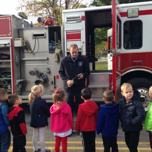 Alumni, Brad showing the PreK4 students some of the tools found on a fire truck.