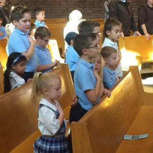 The 4th graders & their Kindergarten buddies saying the Pledge.